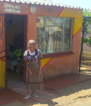 Cesillia Ndana in front of her colourful home.